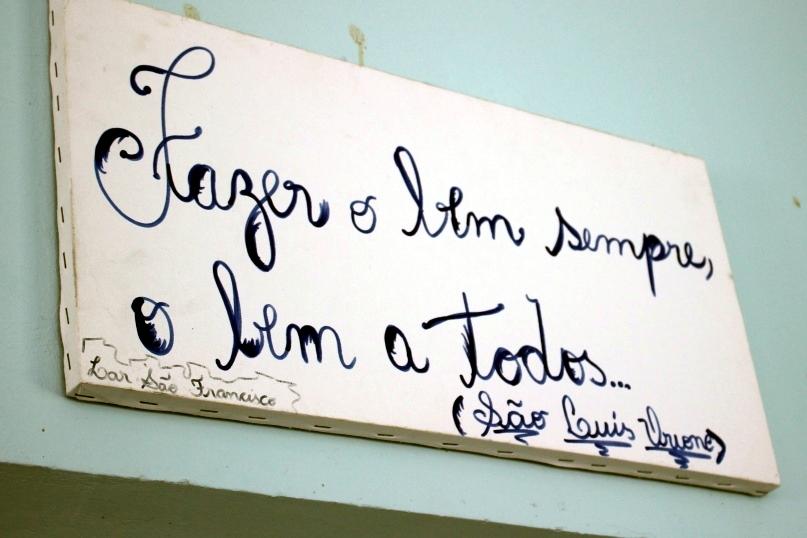 Um dos muitos letreiros afixados no Pequeno Cotolengo com mensagens sobre solidariedade.