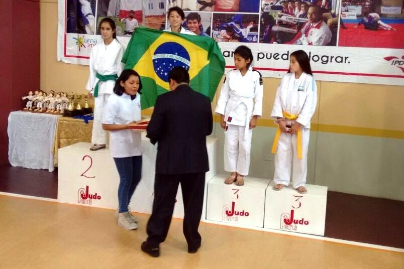 Laura Ayumi Soken comemora a conquista do Campeonato Sul-Americano de Judô Sub-13 com a bandeira do Brasil.