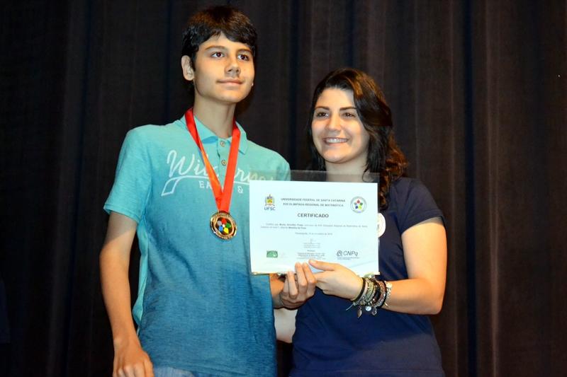 Murilo Schoffen Prado recebe o certicado e a medalha de prata da 17.ª Olimpíada Regional de Matemática.
