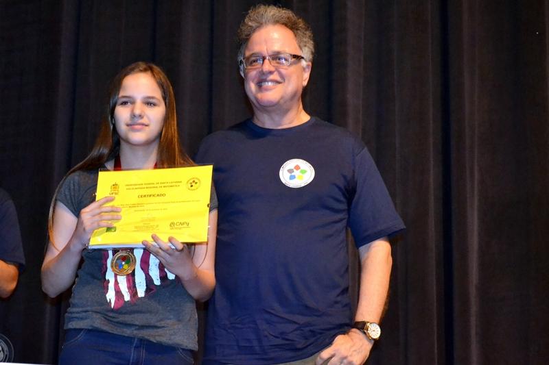 Ana Luiza Demétrio recebe certificado e medalha de ouro da 17.ª Olimpíada Regional de Matemática.